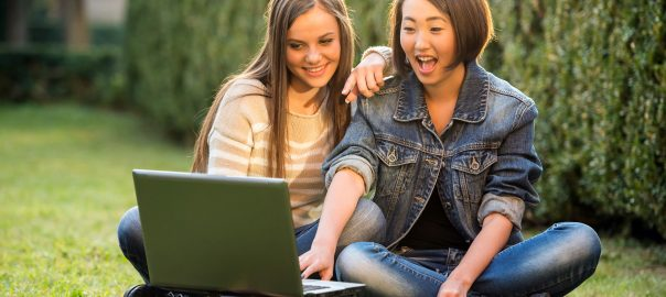 Two woman using laptop in outdoor setting