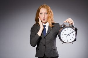 Shocked woman holding a big alarm clock